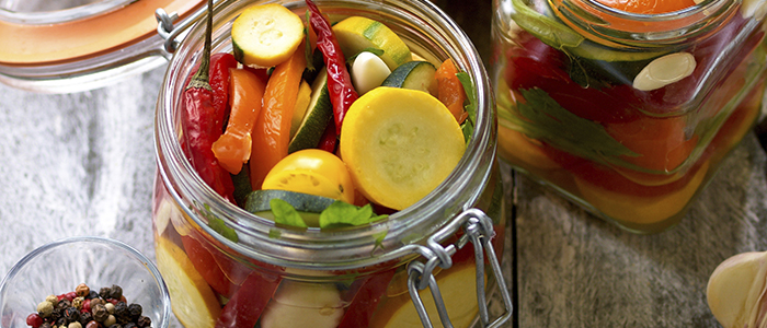 Preparing preserves of pickled zucchini, pepper and tomatoes in jars with spices, garlic and herbs with selective focus