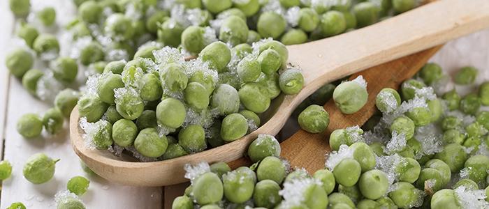 Frozen green peas on wooden background. Selective focus.