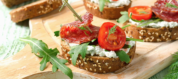 Fresh toast sandwiches with cottage cheese, salami, cherry tomatoes and arugula