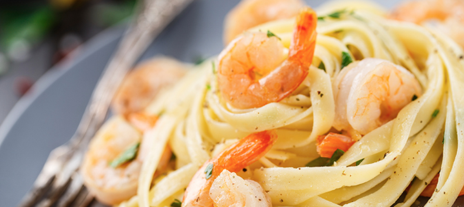Tagliatelle with shrimps and parsley on a plate